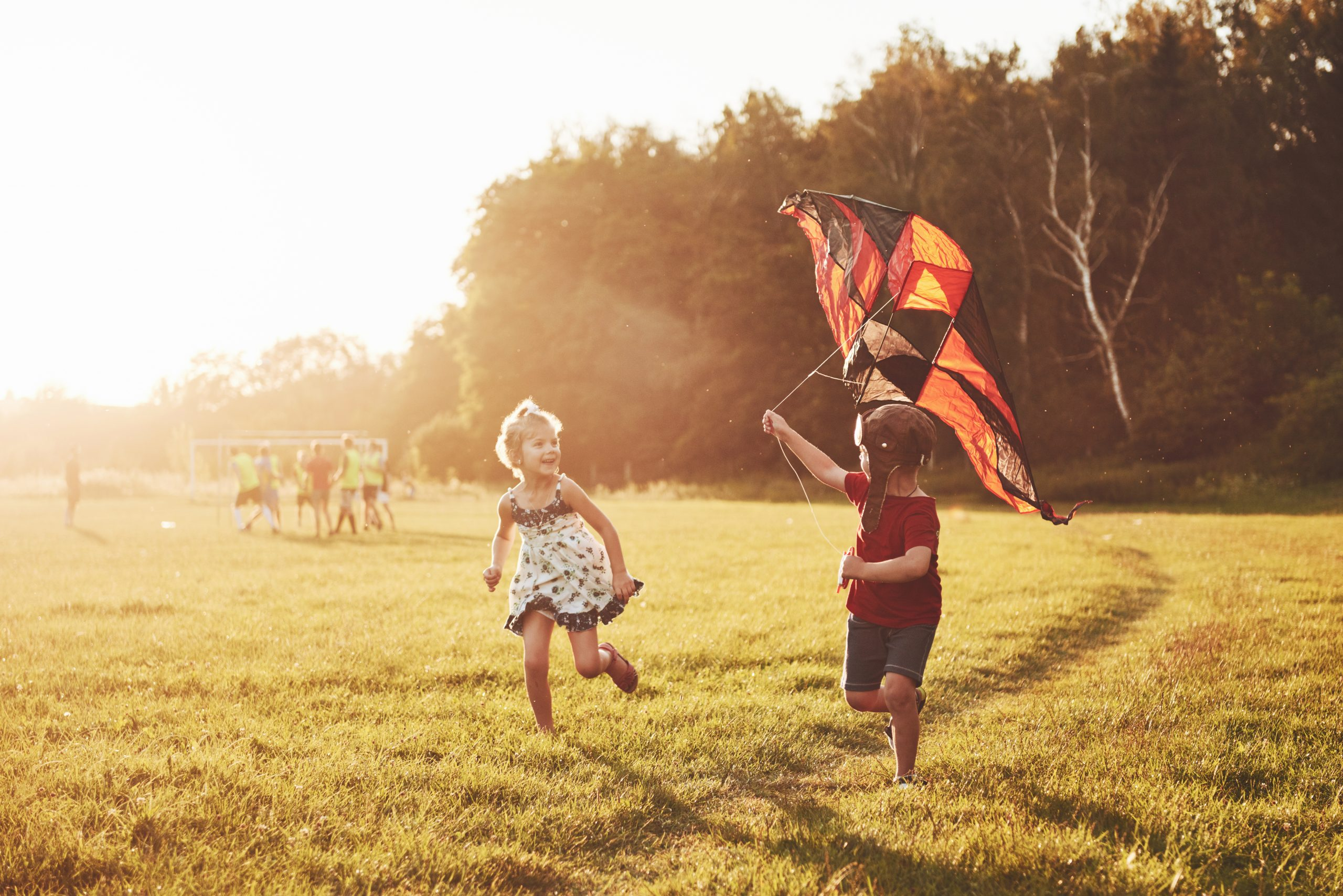 Happy children launch a kite in the field at sunset. Little boy and girl on summer vacation