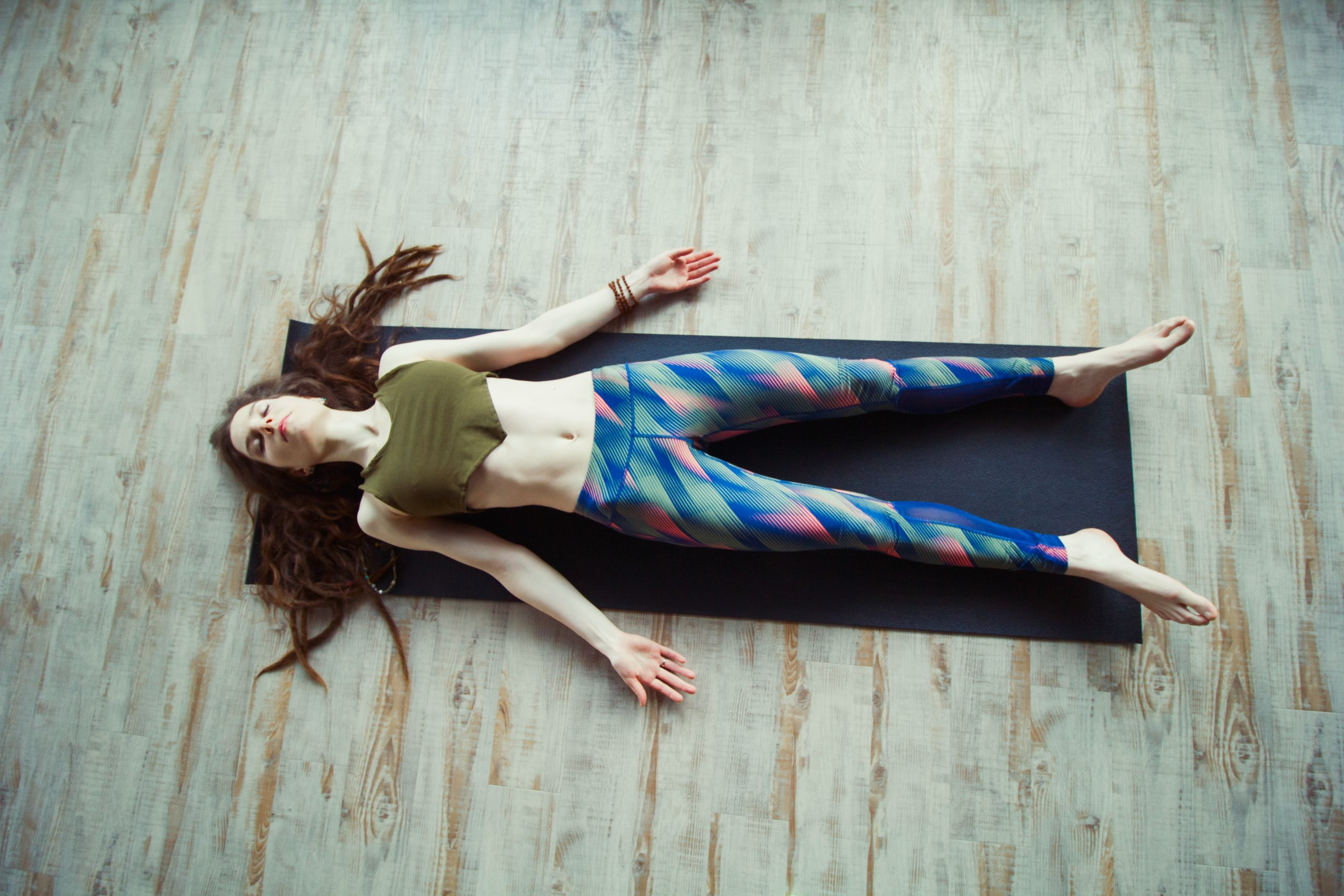 beautiful caucasian woman with long hair and slender body doing yoga on a mat top view ,leisure and relaxation in shavasana position