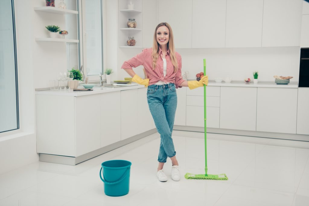 Full length body size photo beautiful nice duties funky she her lady wash white shiny floor finished work wait check expert mind wear jeans denim casual checkered plaid shirt bright light kitchen
