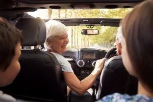Grandparents And Grandchildren Driving In Open Top Car