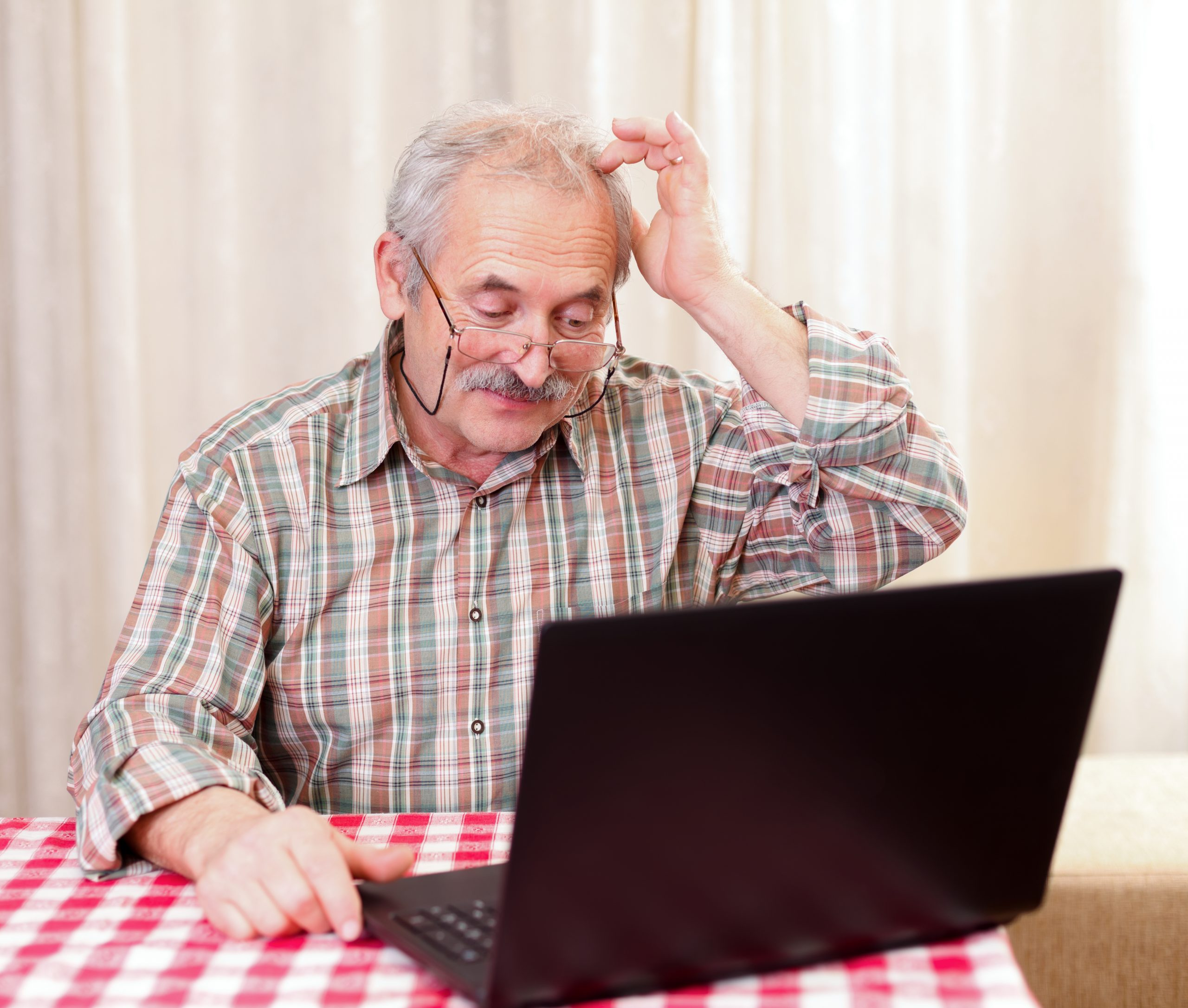 Elderly man using the laptop at home.