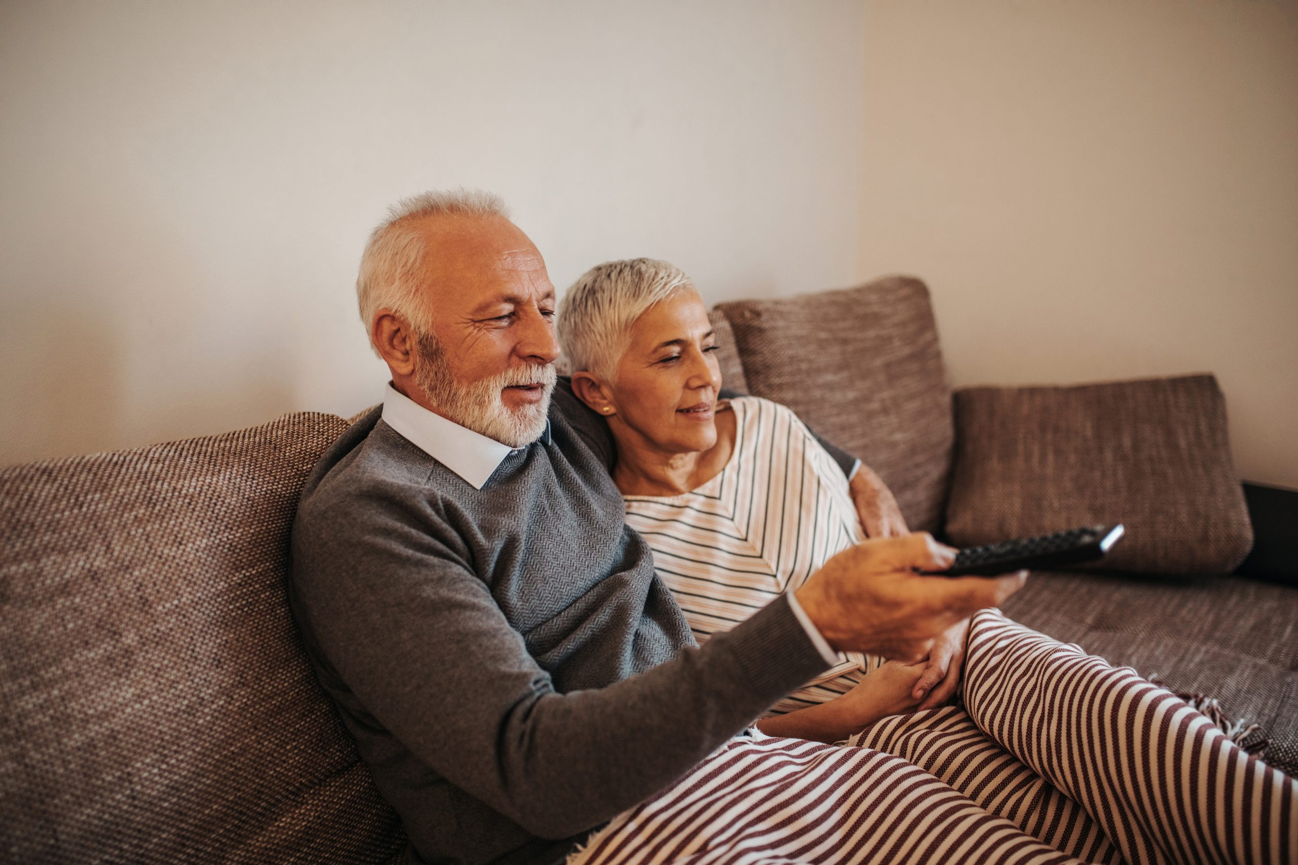Elderly couple watching television at home
